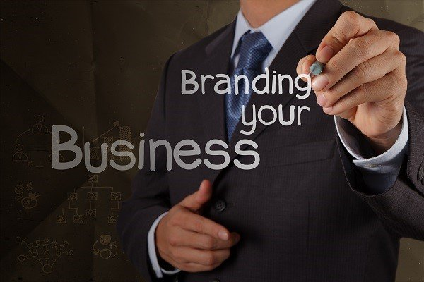 businessman hand writing branding your business with crumpled re